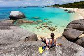 Young woman with snorkeling equipment enjoying view of a tropical beach sitting on granite boulder at Virgin Gorda, British Virgin Islands, Caribbean