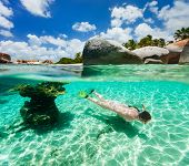 Split photo of young woman snorkeling in turquoise ocean water among corals and tropical fish on Virgin Gorda, British Virgin Islands, Caribbean