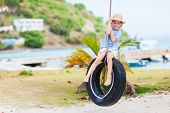 Adorable little girl having fun on tire swing on summer day