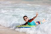Little boy on vacation having fun swimming on boogie board