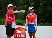 KUALA LUMPUR, MALAYSIA - OCTOBER 11, 2014: Mi Hyang Lee of South Korea listens to her caddy at the fourth hole of the KL Golf & Country Club during the 2014 Sime Darby LPGA Malaysia golf tournament.