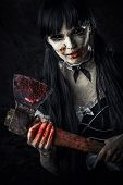 foto of extend  - Dead female zombie with bloody axe extends hand to shot - JPG