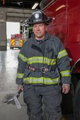 Fully Uniformed FireFighter Holding Gear standing in front of fire truck portrait