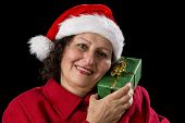 Senior Lady With Santa Claus Hat And Wrapped Gift.