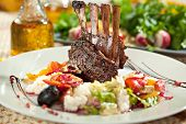 Roasted Lamb Chops with Risotto and Vegetables. Garnished with Sauce