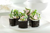Japanese Cuisine - Sushi Roll with Shrimps and Cheese inside. Topped with Cheese and Tobiko and Green Onions
