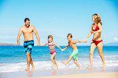 Photo of Happy Family Running Down the Beach