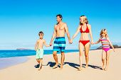 Photo of Happy Family Walking Down the Beach