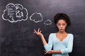 Surprised afro-american woman trying to solve a problem on chalkboard
