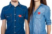 Miling couple standing isolated on white background with paper heart in pocket.