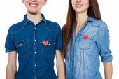 Miling couple standing isolated on white background with paper heart in pocket