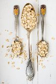 Three Tablespoons Of Oatmeal Lying On A White Wooden Background. Healthy Food.