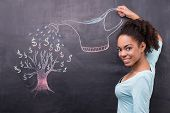 Young afro-american woman watering dollar tree painted on chalkboard