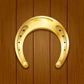 stock photo of horseshoe  - Shiny golden horseshoe on wooden background - JPG