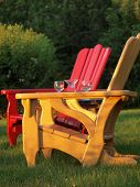 stock photo of wane  - Colorful Adirondack chairs and empty wine glasses seen in the waning sun