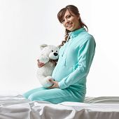 Happy expectant mother in casual clothes with toy