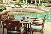 Table And Chairs In Outdoor Cafe Next To The Resort Swimming Pool