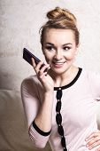 Businesswoman Talking On Mobile Phone On Couch