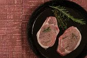 Raw pork steaks with pepper and rosemary