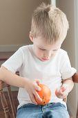 toddler peeling orange
