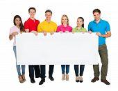 Multiethnic Group Of Friends Showing Blank Billboard