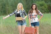 Students girls hitchhiking with cardboard on road