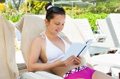 Woman Reading Book On Lounge Chair At Resort