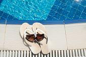 Flip Flops And Sunglasses Beside Swimming Pool