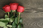 Romantic background with red roses on wood table