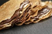 thin crepes or blinis with chocolate cream on slate board