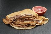 crepes or blinis with chocolate cream and orange on slate board
