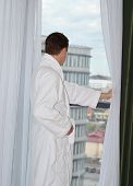Back view of man in white bathrobe standing near  window