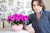 Man sitting at  table and flower room
