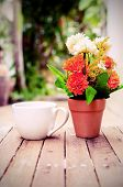 Cup Of Coffee On Wooden Table With Flower