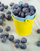 Blueberries In  Small Buckets On A Wooden Table.