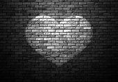 picture of stonewalled  - dimly lit old brick wall enlightened cone of light in the shape of heart - JPG