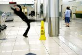 image of slip hazard  - Man slips next to Wet Floor sign - JPG