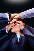 Closeup of business team putting their hands on top of each other