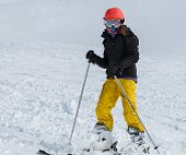 Young Girl (9-11) Skiing In Bright Yellow Pants With Orange Helmet