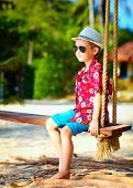 Cute Stylish Boy On Swings On The Beach
