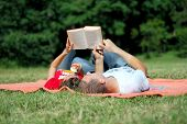 Beautiful Happy Couple Having Picnic and Reading Outside
