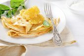 Crepe With Honey And Sour Cream On A Plate