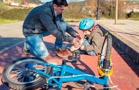 picture of knee  - Father putting a plaster band over knee injury to his son after falling off to the bicycle - JPG