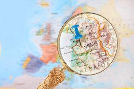 stock photo of albania  - Blue tack on map of Europe with magnifying glass looking in on Tirane Albania - JPG