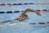 pic of swimming  - Young 10 year old asian girl swims freestyle with goggles and cap in a swimming pool - JPG