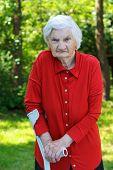 stock photo of crutch  - Handicap elderly woman using a crutch to walk - JPG