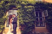 pic of ivy  - Bride and groom embracing in front of a beautiful house covered with ivy