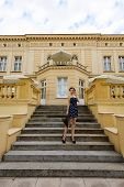 pic of old lady  - vintage fashion shot of young and beautiful lady in elegant blue dress outside near an old palace  - JPG