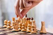 stock photo of chessboard  - hand of chess player near chessboard with pieces - JPG