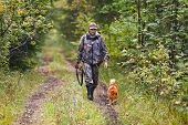 foto of hunter  - hunter with dog walking on the forest road - JPG